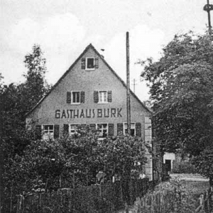 """Gasthaus Burk, auch """"Zum Gelben Löwen"""" Oberbaimbacher Weg 11. Rechts im Bild ist der Kirchweihbaum erkennbar. - Foto: Ausschnitt aus Postkarte, Privatbesitz Burbach"""